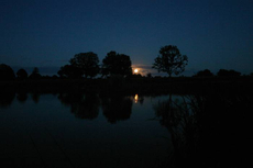 The moon rises over a calm Etang Bertie